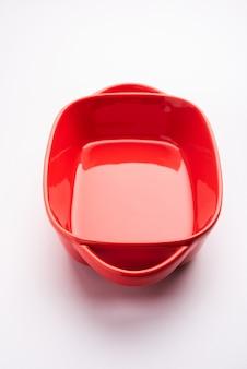 空の食器-白い表面に食べ物のない赤いセラミックボウルまたは耐熱皿