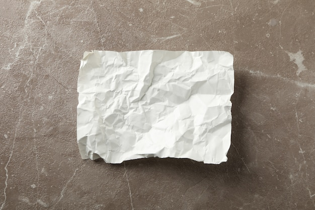 Empty crumpled paper on grey background, top view