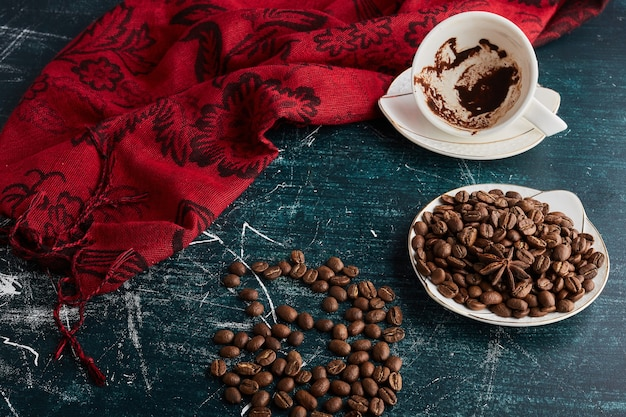 An empty cup of coffee with beans.