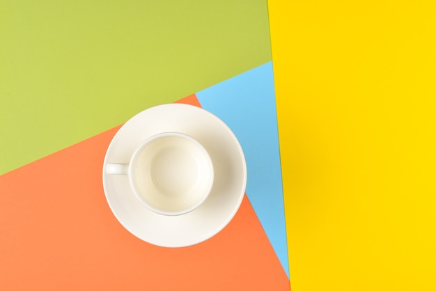 Пустая чашка на красочном фоне.