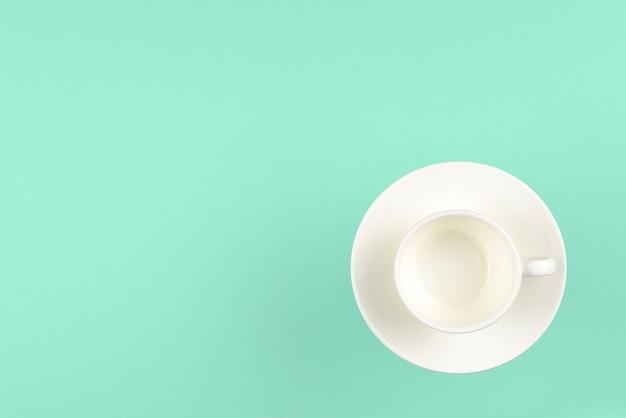 Пустая чашка на зеленом фоне. место для текста или дизайна.
