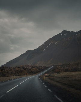 Empty curvy road next to a beautiful rocky mountain under a gray gloomy sky