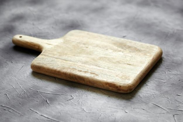 Пустая разделочная доска из соснового дерева на каменном столе, серый фон, вид сбоку