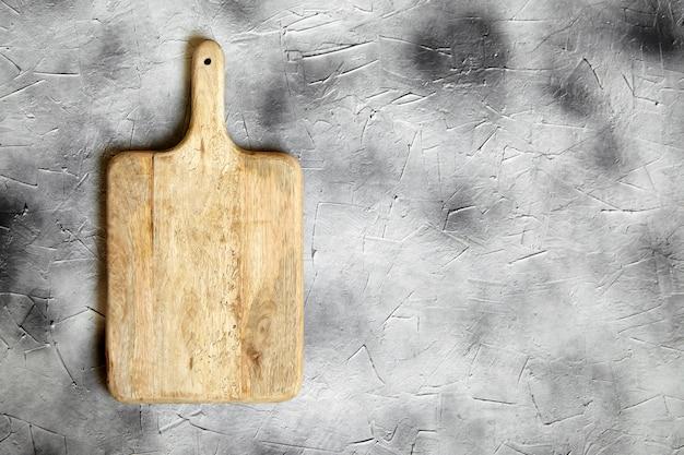 Пустая разделочная доска из соснового дерева на каменном столе, серый фон, вид сверху