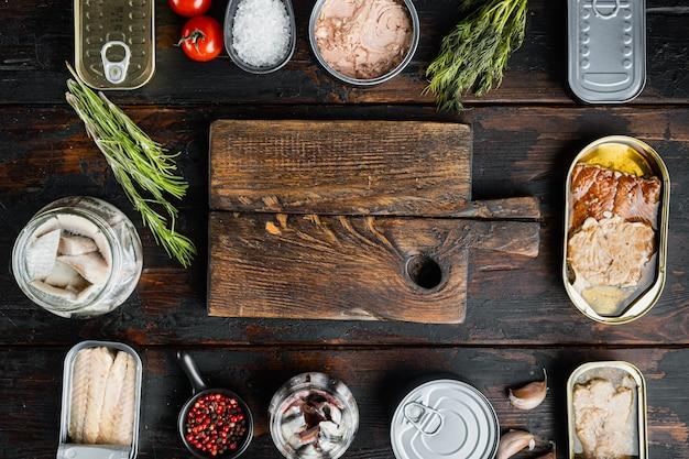 Пустая разделочная доска в рамке из морепродуктов консервированной рыбы, на старом темном деревянном столе