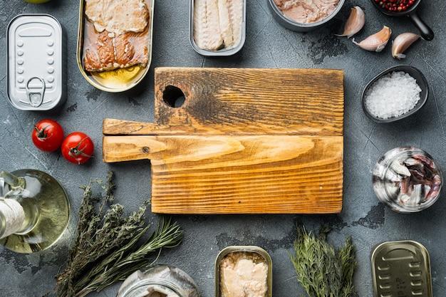 Пустая разделочная доска в рамке набора рыбных консервов, морепродуктов, на сером