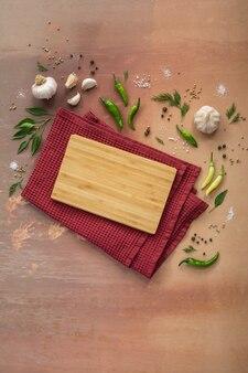 빈티지 테이블에 향신료 마늘 피망과 수건에 빈 커팅 보드