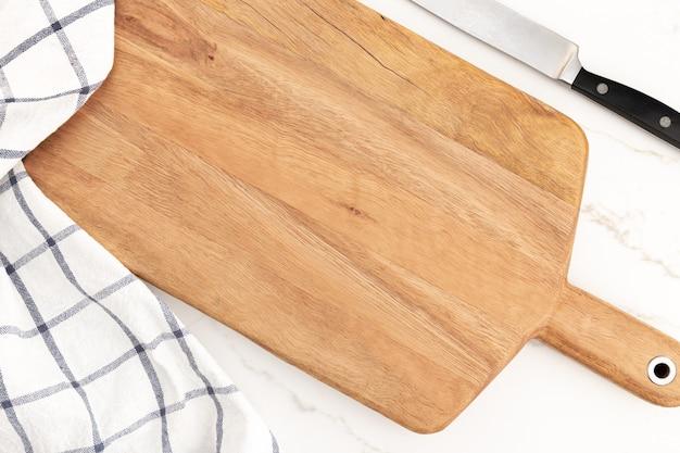 白い大理石の背景の空のカッティングボード。料理キッチンの背景。モックアップ
