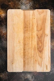Набор пустых разделочных досок, на старом темном деревенском фоне стола, плоская планировка, вид сверху, с копией пространства для текста или вашего продукта