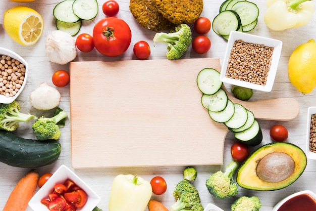Empty cutting board surrounded by veggie food