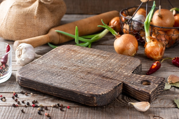Empty cutting board with with ingredients on wooden background. place for your object