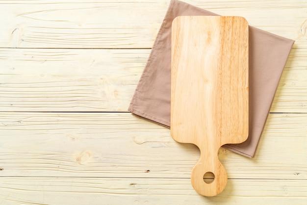 Пустой разделочная деревянная доска на фоне кухонной ткани