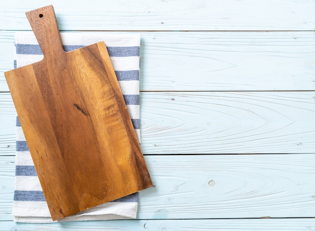 Empty cutting wooden board with kitchen cloth on wooden background, top view