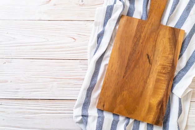 Пустая разделочная деревянная доска с кухонной тканью