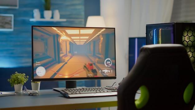 온라인 e스포츠 토너먼트를 준비하는 책상에 사람이 없는 게임 스튜디오의 화면에 1인칭 슈팅 게임이 있는 rgb 강력한 개인용 컴퓨터가 있는 빈 사이버 공간. 사람이 없는 방