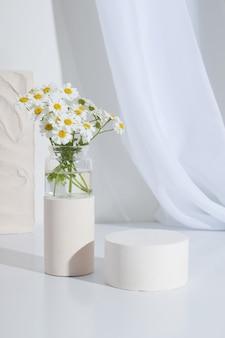 흰색 배경에 카모마일 꽃이 있는 빈 원통형 코 받침대. 빈 선반 제품 서 배경
