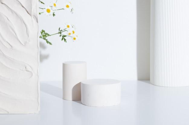흰색 배경에 카모마일 꽃이 있는 빈 원통형 연단 또는 받침대. 빈 선반 제품 서 배경