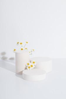 白い背景にカモミールの花が付いた空の円筒形の表彰台または台座。空白の棚製品立っている背景