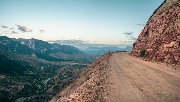 空の危険な狭い崖の山道。山の端と急な崖に沿って運転する危険なオフロード。ダゲスタン。