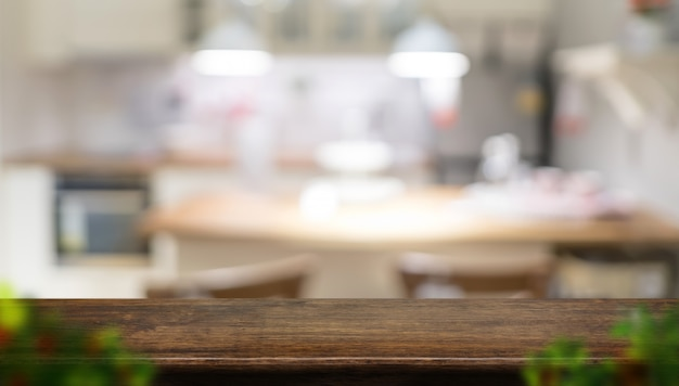 Empty dark brown wooden table top with blurred home kitchen with blur foreground leaf