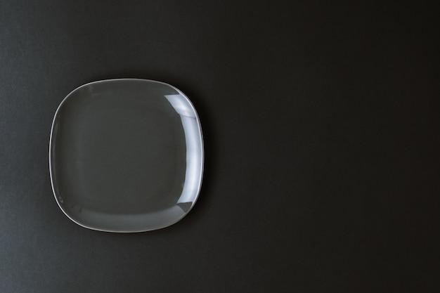 Пустая темно-серая керамическая тарелка, изолированная на черном