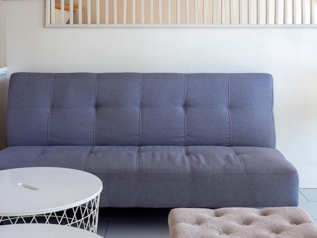 Пустой темно-серый тканевый диван возле современного белого круглого столика и квадратного сиденья на белой стене в гостиной, уютная мебель с чистым и минималистичным дизайном интерьера.