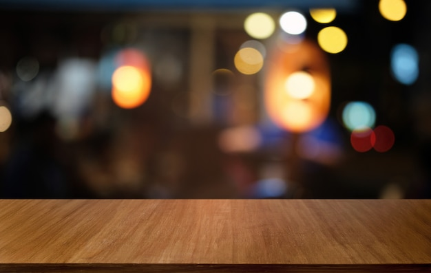 Empty dark wooden table in front of abstract blurred bokeh background of restaurant.