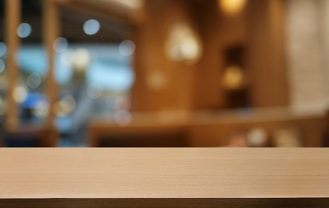 Empty dark wooden table in front of abstract blurred bokeh background of restaurant