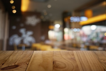 Empty dark wooden table in front of abstract blurred background of cafe and coffee shop interior. can be used for display or montage your products.