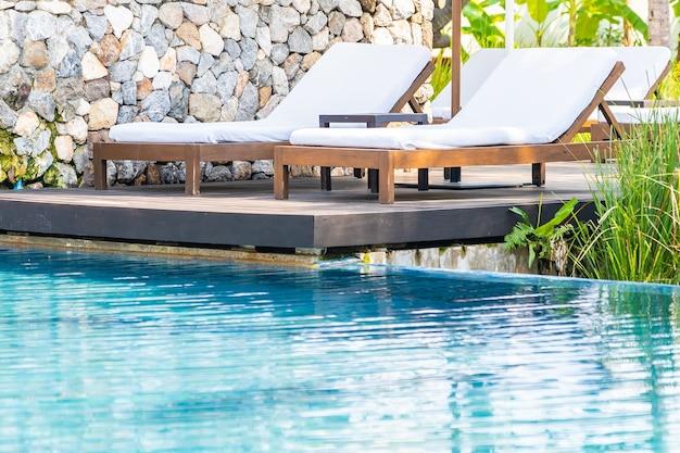 레저 휴가를위한 호텔 리조트의 야외 수영장 주변에 빈 갑판 의자