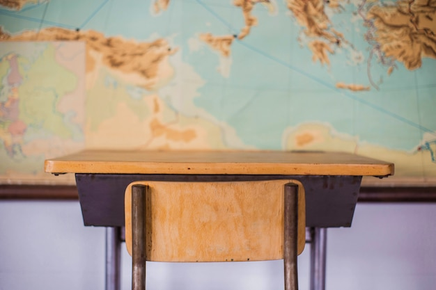 Empty desks at school classroom with world map.