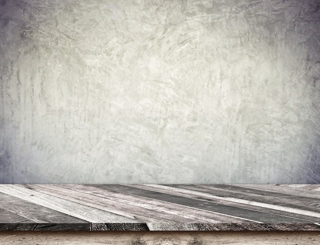 Empty diagonal wood plank table top with grunge concrete wall