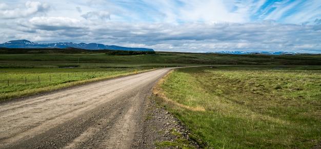 Пустая грязная улица через ландшафт сельской местности.