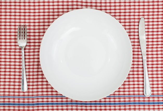 The empty dish with folk and knife on red table.