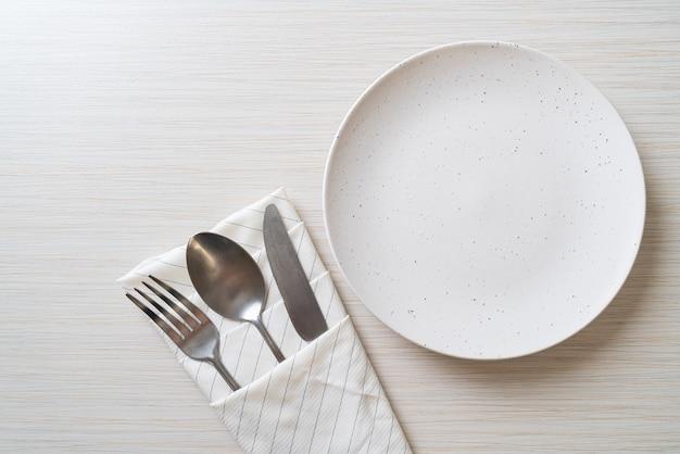 木製のタイルの表面にナイフ、フォーク、スプーンで空の皿