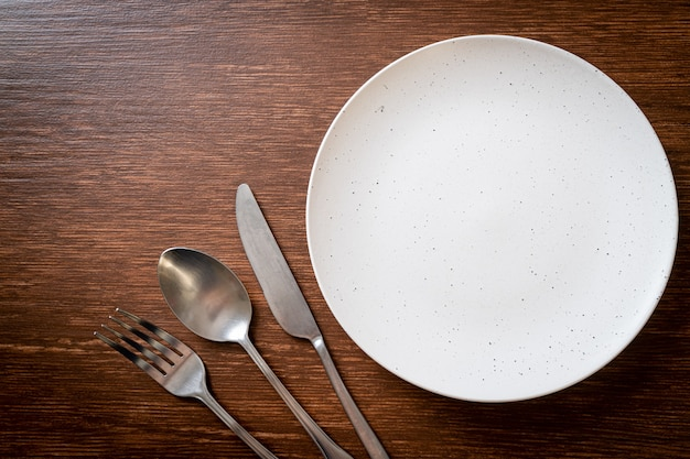 Empty dish with knife, fork and spoon on wood tile surface