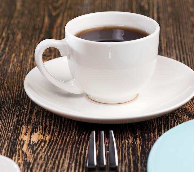 テーブルの上の空の皿とコーヒーマグ、テーブルの設定の空のガラス製品