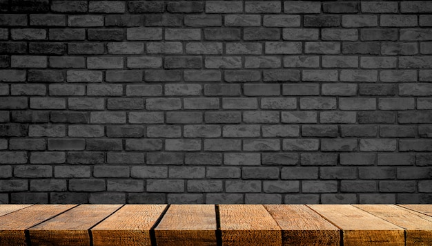 Empty display wooden board shelf table counter with copy space for advertising backdrop and background with black brick wall in the background,