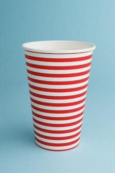 青い背景の上の空の使い捨てパーティーカップ
