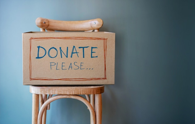 Empty donate box on chair against wall