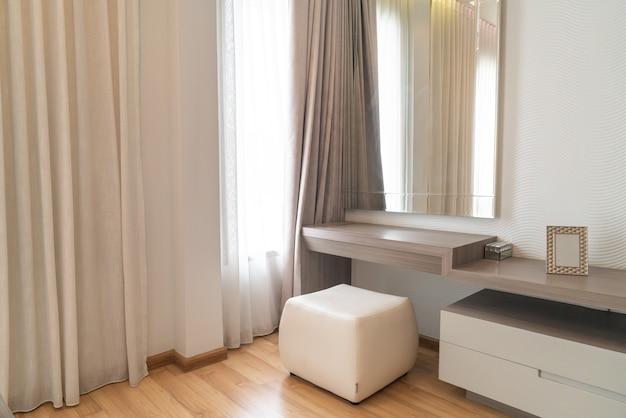 Пустой туалетный столик с зеркалом и занавеской в спальне