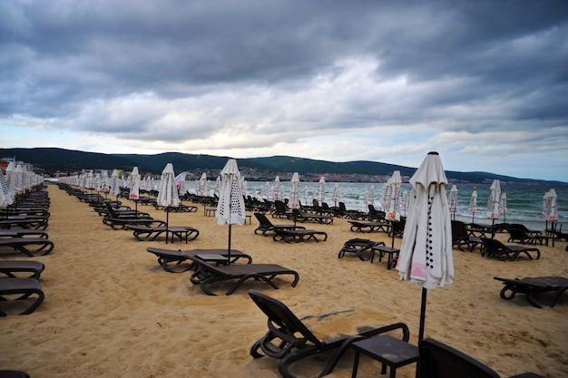 Пустой пустой пляж со сложенными зонтиками