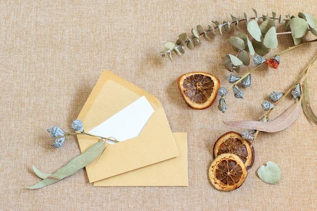 삼베 섬유 배경, 마른 감귤 및 유칼립투스 잎에 빈 봉투
