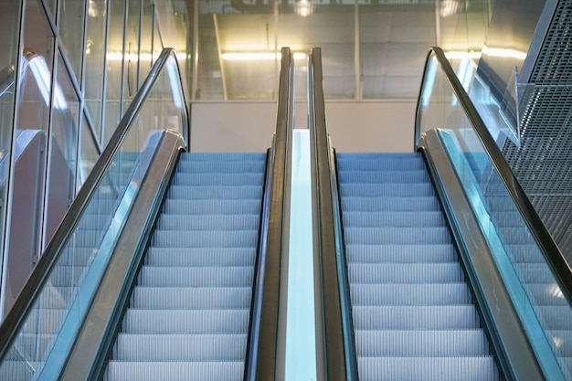 Пустой эскалатор лестницы. современный эскалатор в торговом центре, эскалатор универмага. пустой эскалатор внутри стеклянного здания.