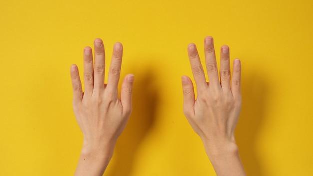 黄色の背景に空の女性の手。