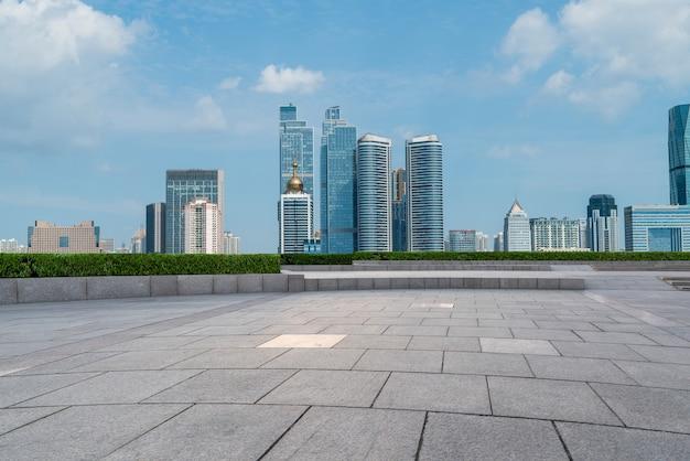 Пустая напольная плитка и горизонт городских зданий