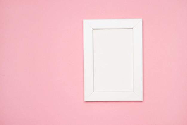 空のフレームと花フラットはピンクのパステルカラーの背景に横たわっていたコピースペースの最小限のコンセプトピンクの背景の家の装飾のフォトフレームのモックアップ