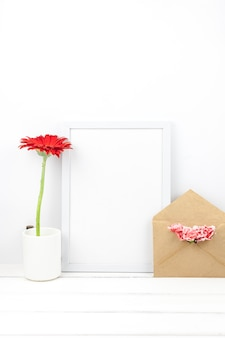 Empty frame; cup; flowers and envelope over wooden table