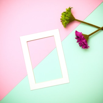 Empty frame and flowers flat lay on pastel background.minimal concept.