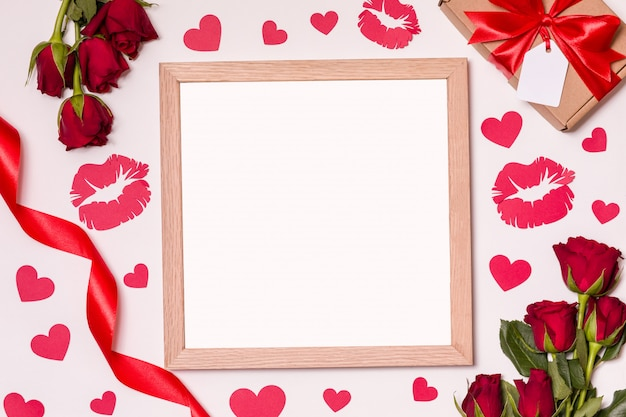 Empty frame mock up on valentines day background with red roses, hearts and kisses.